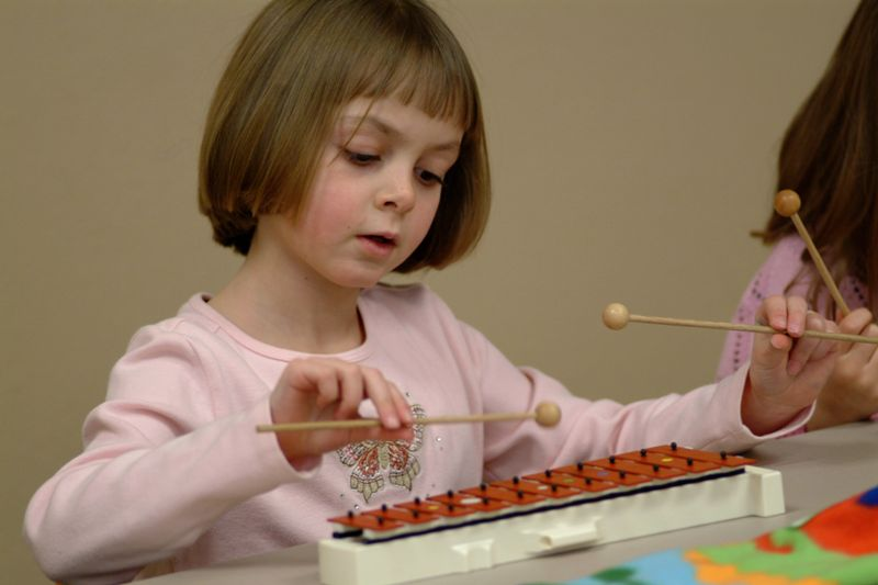 A Kindermusik Young Child student playing the glockenspiel.