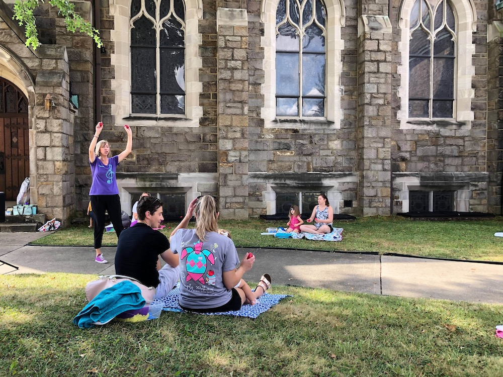 Kindermusik Educator, Christa Beck, leads families through engaging, distanced outdoor music classes.