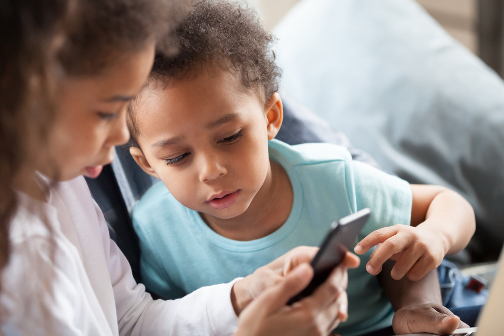 Siblings look at content on a smartphone together. While screen time should be closely monitored, it can have major benefits to early development.